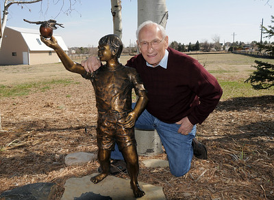 Joseph Mazzola, Heart of Broomfield Philanthropic winner, poses with a statue of a boy reaching for an apple, given to him by his children at his home in Pony Estates. Mazzola said you should reach for your goals but always give back.  March 24, 2011 staff photo/David R. Jennings