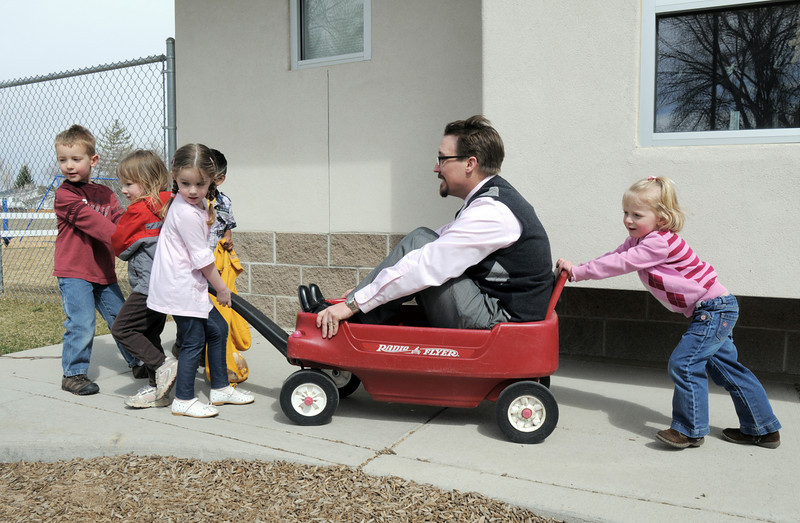 Heart of Broomfield education winner, Brian Conly, director of Bal Swan Children's Center,  is pulled in a red wagon by  Alex Schmidt, left, Evy Huttner, Keeley Williams, Noah Gudise with Hannah Anderson pushing during play time.<br /> <br /> March 30, 2011<br /> staff photo/David R. Jennings
