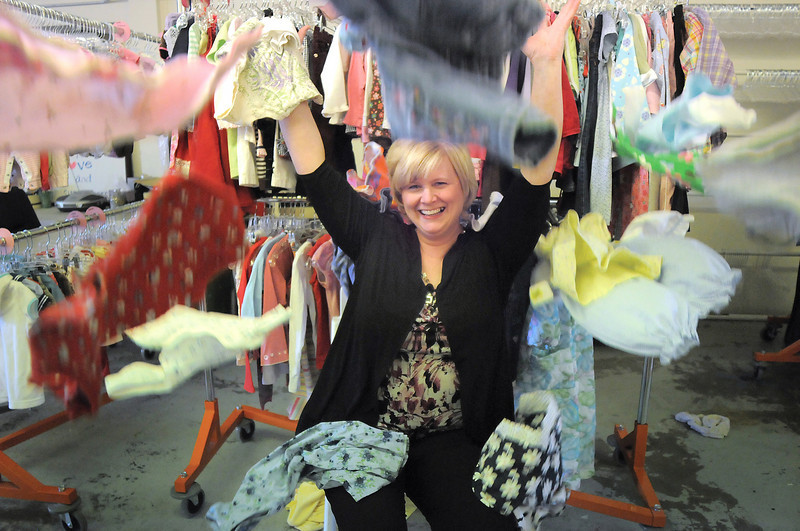 Carina Martin, Heart of Broomfield Angel award, reaches while being showered by children's cloths at A Precious Child.<br /> <br /> March 29, 2011<br /> staff photo/David R. Jennings