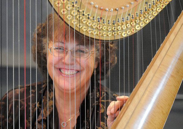 Nancy Brace Heart of Broomfield Arts winner looks through the string of her harp named Cassandra at the Rocky Mountain Center for Musical Arts in Lafayette.<br /> April 9, 2011<br /> staff photo/David R. Jennings