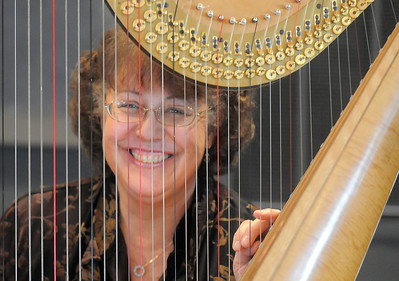 Nancy Brace Heart of Broomfield Arts winner looks through the string of her harp named Cassandra at the Rocky Mountain Center for Musical Arts in Lafayette. April 9, 2011 staff photo/David R. Jennings