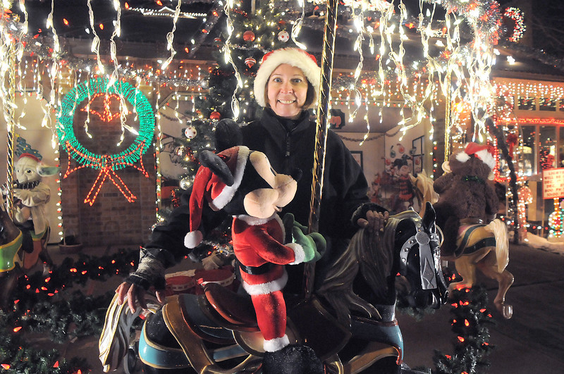 "Kim Weibert  poses with the carousel a new addition to her holiday lighting display at 1188 Clubhouse Drive. The carousel was buiilt by her father-in-law Marvin Hart in memory of Kim's partner Kevin Hart who died n Christmas day last year. Each horse on the carousel in painted a named after horses Kevin rode as a child. They are named Jared, Applesauce, Vetta and Blackie.<br /> More photos please see  <a href=""http://www.broomfieldenterprise.com"">http://www.broomfieldenterprise.com</a><br /> December 9, 2011<br /> Staff photo/ David R. Jennings"