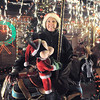 """Kim Weibert  poses with the carousel a new addition to her holiday lighting display at 1188 Clubhouse Drive. The carousel was buiilt by her father-in-law Marvin Hart in memory of Kim's partner Kevin Hart who died n Christmas day last year. Each horse on the carousel in painted a named after horses Kevin rode as a child. They are named Jared, Applesauce, Vetta and Blackie.<br /> More photos please see  <a href=""""http://www.broomfieldenterprise.com"""">http://www.broomfieldenterprise.com</a><br /> December 9, 2011<br /> Staff photo/ David R. Jennings"""