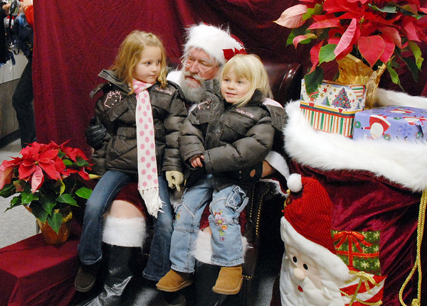 Hadley Olsen, 5, left, and her sister Samantha, 3, tell Santa their wishes at the Holiday Tree Lighting Ceremony at the Broomfield City and County Building on Friday<br /> December 4, 2009<br /> Staff photo/David R. Jennings
