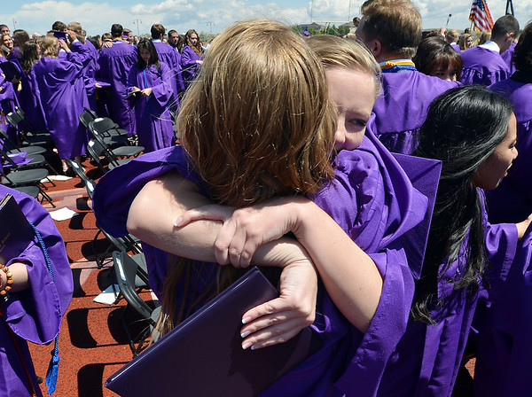 Kyrie Hill, right, hugs Mckenzie Zeman after Holy Family High School's 87th Annual Commencement at Mike G. Gabriel Stadium on Thursday.<br /> <br /> May 24, 2012 <br /> staff photo/ David R. Jennings