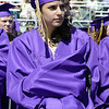 Gina Cannella wraps herself in her robe to stay warm from the wind blowing during Holy Family High School's 87th Annual Commencement at Mike G. Gabriel Stadium on Thursday.<br /> <br /> May 24, 2012 <br /> staff photo/ David R. Jennings