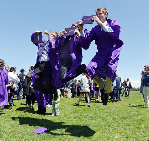 Taylor Coletta, left, C.J. Koral and Daniel Ray jump in the air holding their diplomas for a picture by family members after Holy Family High School's 87th Annual Commencement at Mike G. Gabriel Stadium on Thursday.<br /> <br /> May 24, 2012 <br /> staff photo/ David R. Jennings