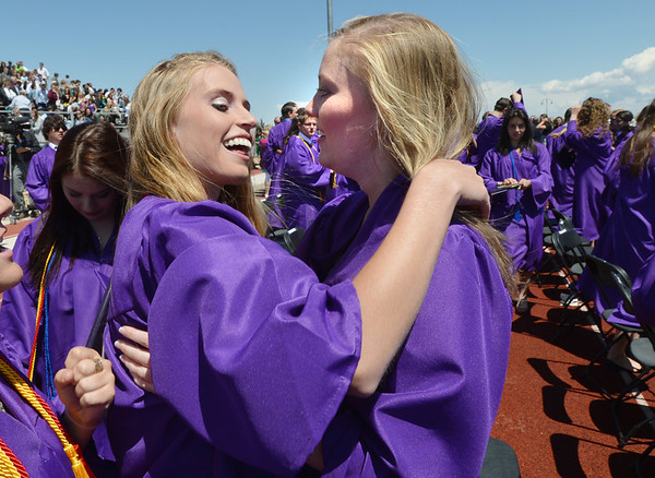 Mckenzie Zeman, left, celebrates with Kyrie Hill after Holy Family High School's 87th Annual Commencement at Mike G. Gabriel Stadium on Thursday.<br /> <br /> May 24, 2012 <br /> staff photo/ David R. Jennings