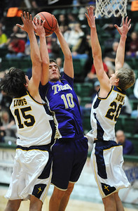 Holy Family's Tanner Stuhr goes to the basket against Colorado Springs Christian's Reagan Chapman, left, and Ryan Russell during the 3A state Great Eight Game at CSU on Thursday.  March 8,  2012  staff photo/ David R. Jennings