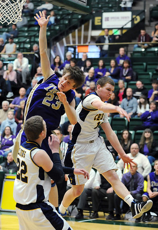 Holy Family's Ryan Willis goes to the basket against Colorado Springs Christian's Evan McConell and Reagan Chapman during the 3A state Great Eight Game at CSU on Thursday.<br /> <br /> March 8,  2012 <br /> staff photo/ David R. Jennings