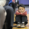 A family member of a graduate watches the cremony sitting on the floor of the gym during Wednesday's Holy Family High School graduation ceremony.<br /> May 18, 2011<br /> staff photo/David R. Jennings
