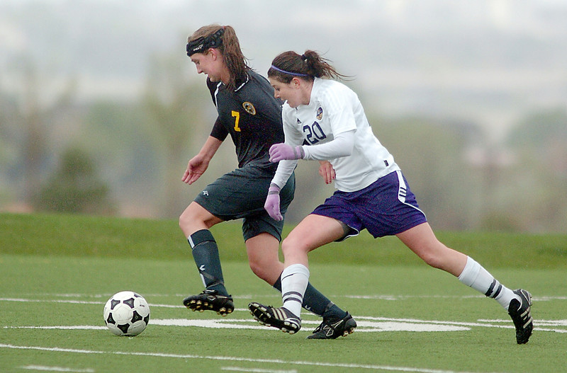 Holy Family's Abby Metzger fights for control of the ball with Manitou Springs' Calla Urban during the state playoff game at the Broomfield County Commons Park on Thursday.<br /> May 19, 2011<br /> staff photo/David R. Jennings