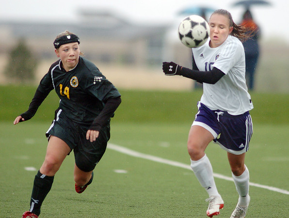 Holy Family's Meghan Jonikas runs to the ball ahead of Ashley Benson,  Manitou Springs during the state playoff game at the Broomfield County Commons Park on Thursday.<br /> May 19, 2011<br /> staff photo/David R. Jennings