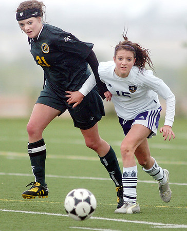 Holy Family's Maddie Kuzik fights for control of the ball with Maddie Snowden, Manitou Springs, during the state playoff game at the Broomfield County Commons Park on Thursday.<br /> May 19, 2011<br /> staff photo/David R. Jennings