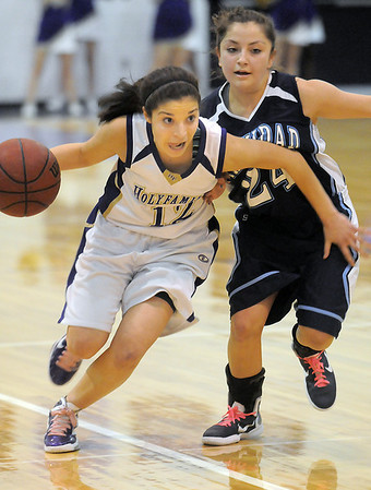 Holy Family's Megan Chavez drives the ball down court against Trinidad's Chelsea Velaquez during the Class 3A sweet 16 game at Holy Family on Saturday.<br /> March 5, 2011<br /> staff photo/David R. Jennings