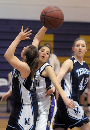 Holy Family's Megan Chavez passes the ball away from Trinidad's Justine Gallegos and Molly Roth during the Class 3A sweet 16 game at Holy Family on Saturday.<br /> March 5, 2011<br /> staff photo/David R. Jennings