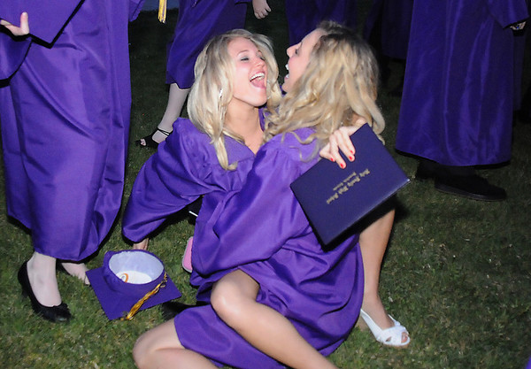 Stacey Harward, left, and Melanie Coletta on the ground after giving each other a hug after Wednesday's 85th annual Holy Family HIgh School graduation at Holy Family.<br /> May 19, 2010<br /> Staff photo/ David R. Jennings