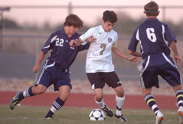 Holy Family's Preston Arguello fights for control of the ball against Kent Denver's Marcus Stears, left, and Cole Evans during Thursday's game at Michael G. Gabreal Stadium.<br /> October 13, 2011<br /> staff photo/ David R. Jennings