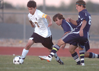 Holy Family's Preston Arguello takes control of the ball from Kent Denver's Marcus Stears and Cole Evans during Thursday's game at Michael G. Gabreal Stadium. October 13, 2011 staff photo/ David R. Jennings