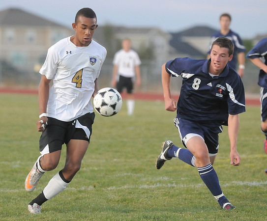 Holy Family's Nick Rhoden dribbles the ball past Kent Denver's Sam Wittmer during Thursday's game at Michael G. Gabreal Stadium.<br /> October 13, 2011<br /> staff photo/ David R. Jennings