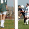 Tarah Neam, Holy Family, kicks the ball toward the goal past Megan Moran, Bishop Machebeuf, during Wednesday's game at Machebeuf.<br /> <br /> April 14, 2010<br /> Staff photo/David R. Jennings