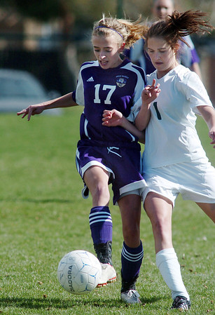 Holy Family's Monica Stokes takes control of the ball against Monica Paolucci, Bishop Machebeuf, during Wednesday's game at Machebeuf.<br /> <br /> April 14, 2010<br /> Staff photo/David R. Jennings