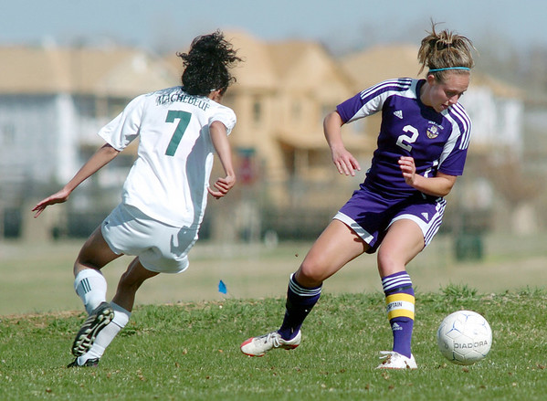 Kristina Burk, Holy Family, keeps an eye on the ball as she moves out of the corner past Alex Griffin, Bishop Machebeuf, during Wednesday's game at Machebeuf.<br /> <br /> April 14, 2010<br /> Staff photo/David R. Jennings
