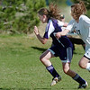 Heidi Hanson, Holy Family, takes the ball downfield past Emily Garcia, Bishop Machebeuf, during Wednesday's game at Machebeuf.<br /> <br /> April 14, 2010<br /> Staff photo/David R. Jennings