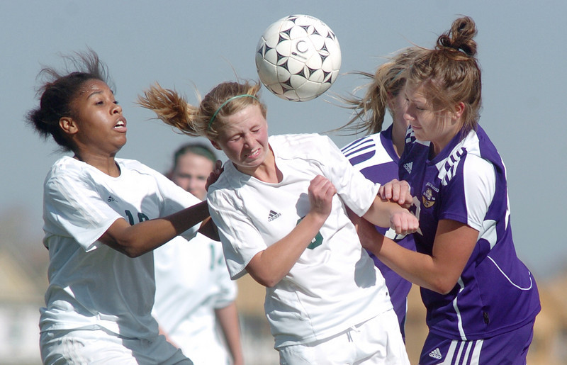 Holy Family's Amy Baumberger does a header over Bishop Machebeuf's Spencer Sherman and Theresa Hegarty during Wednesday's game at Machebeuf.<br /> <br /> April 14, 2010<br /> Staff photo/David R. Jennings