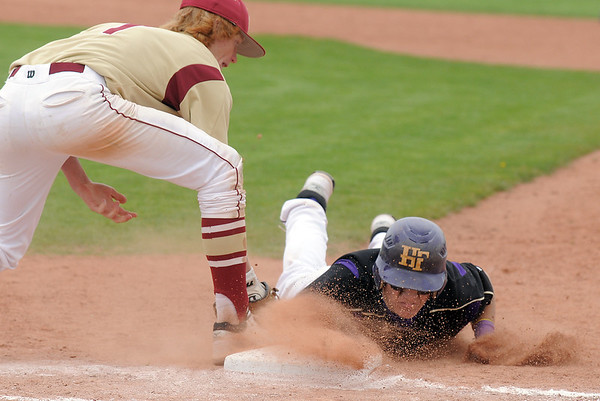 Garrett West, Holy Family, slides back to first base but was tagged out by Tyler Tucker, Faith Christian, in a controversial play during the state 3A championship game at Jackson Field in Greeley on Saturday.<br /> May 28, 2011<br /> staff photo/David R. Jennings