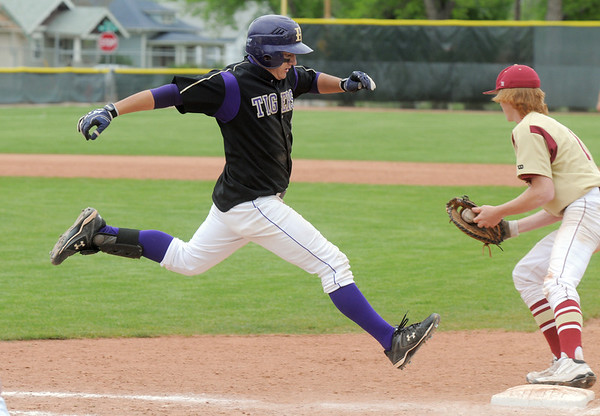 Joe Walls, Holy Family leaps to first base trying to beat the ball thrown to Tyler Tucker, Faith Christian first baseman during the state 3A championship game at Jackson Field in Greeley on Saturday.<br /> May 28, 2011<br /> staff photo/David R. Jennings