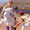 After getting caught between players, Holy Family's Jay Elliott squeeks by Faith Christian's Isaac Henry and David Bote during Saturday's double header at Holy Family.<br /> April 16, 2011<br /> staff photo/David R. Jennings