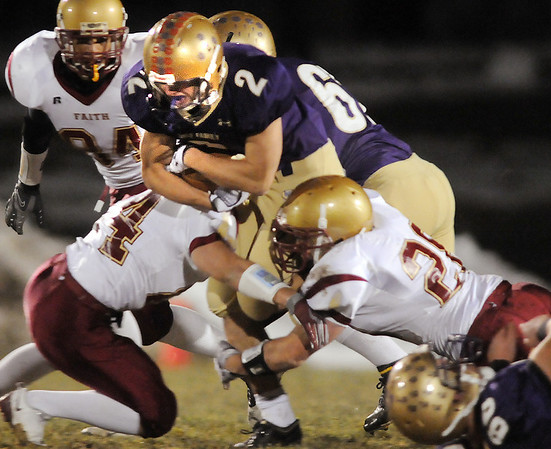 Jonathon Gerry,  Holy Family is tackled by Andy Clement and Richard Rush, Faith Christian during Friday's game at Mike G. Gabriel Stadium.<br /> October 30, 2009<br /> Staff photo/David R. Jennings
