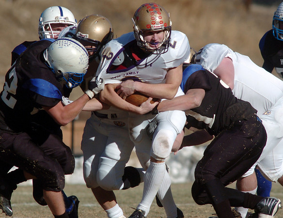 Holy Family's Jonathon Gerry is tackled by Andy Magelky, left, and Blake Hoiberg, Platte Canyon during Saturday's game at Platte Canyon High.<br /> November 21, 2009<br /> Staff photo/David R. Jennings