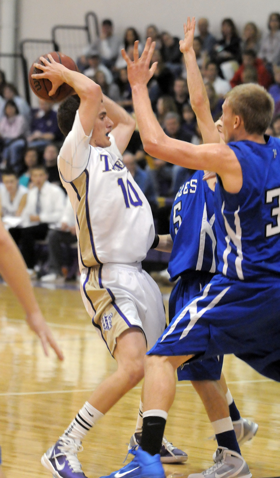 Holy Family's Tanner Stuhr goes against Broomfield's Dakota Smith and Austin Wood during Saturday's cross town game at Holy Family.<br /> <br /> January 29, 2011<br /> staff photo/David R. Jennings