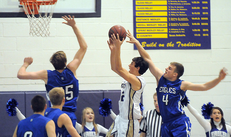 Holy Family's Nate Golter shoots to the basket past Broomfeild's Aric Kaiser during Saturday's cross town game at Holy Family.<br /> <br /> January 29, 2011<br /> staff photo/David R. Jennings