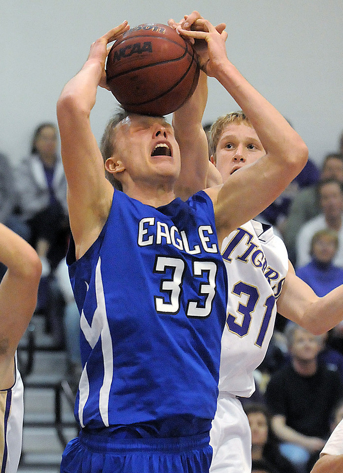 Broomfield's Dakota Smith tires to get the ball to the basket against Holy Family's Gintas Jarasius during Saturday's cross town game at Holy Family.<br /> <br /> January 29, 2011<br /> staff photo/David R. Jennings