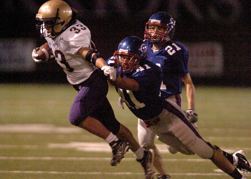 Holy Family's Clay Connor breaks away from a tackle by Centaurus' Eric Hatlen during Friday's game at Centaurus High in Lafayette.<br /> <br /> September 24, 2010<br /> staff photo/David R. Jennings