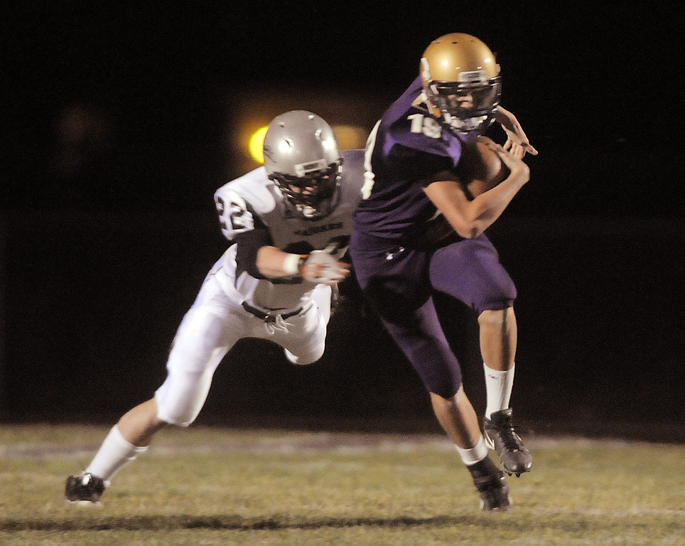 Holy Family's quarterback Zach Langfield tries escape a tackle by D' Evelyn's Colton Hall during Friday's game at Michael G. Gabriel Stadium.<br /> October 29, 2010<br /> staff photo/David R. Jennings