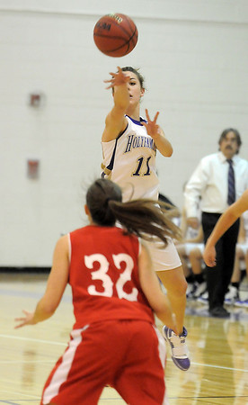 Taylor Helbig, Holy Family, passes the ball over Beth Cheney, Eaton during Tuesday's game at Holy Family.<br /> January 4, 2011<br /> staff photo/David R. Jennings