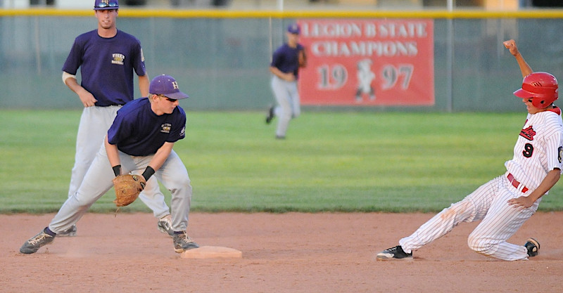 Connor Meining, shortstop, Holy Family, reaches second base as Cory Dyer, Eaton, makes a slide to the base during the state Legion B baseball playoffs Thursday at Eaton High School.<br /> <br /> July 23, 2009<br /> staff photo/David Jennings