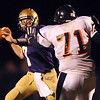 Quarterback Joe Sommers, Holy Family, looks for an open reciever as Brandyn Neumann, Erie advances during play at Mike G. Gabriel Stadium on Friday.<br /> <br /> Sept. 25, 2009<br /> Staff photo/David R. Jennings