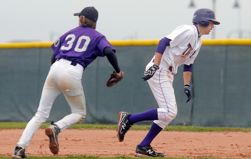 Holy Family's Devlin Granberg runs back to first base past Estes Park's Conner Bryant during Saturday's district game at Holy Family.<br /> May 14, 2011<br /> staff photo/David R. Jennings