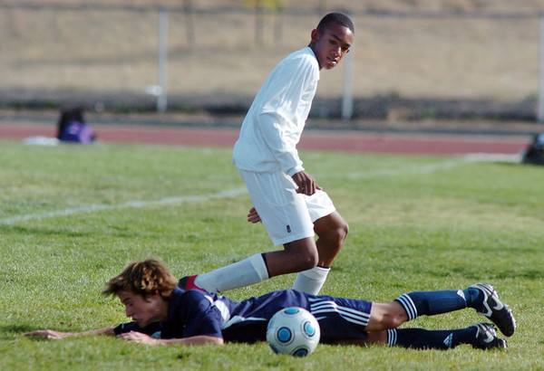 Nicholas Rhoden, Holy Family, goes for the ball after Sam Wittmer, Kent Denver, falls during play at Mike G. Gabriel Stadium on Tuesday.<br /> <br /> Sept. 29, 2009<br /> Staff photo/David R. Jennings