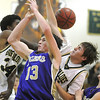 Josh Tinnon, Holy Family, fights for the ball against  evon White and Andy Gartland, Bishop Machebeuf, during Thursday's game at Machebeuf.<br /> <br /> <br /> January 21, 2010<br /> Staff photo/David R. Jennings