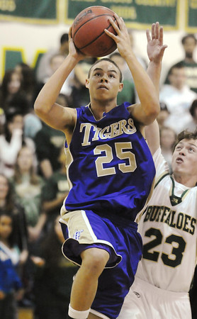 Jeremiah Haynes, Holy Family, goes up for two against Jack Heher, Bishop Machebeuf during Thursday's game at Machebeuf.<br /> <br /> <br /> January 21, 2010<br /> Staff photo/David R. Jennings