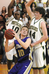 Bryan Murphy, Holy Family, pauses before going to the basket past Fitsum Melles and Casey Kipp, Bishop Machebeuf, during Thursday's game at Machebeuf.   January 21, 2010 Staff photo/David R. Jennings