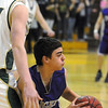 Nick Bovine, Holy Family, looks for an open player past Casey Kipp, Bishop Machebeuf during Thursday's game at Machebeuf.<br /> <br /> <br /> January 21, 2010<br /> Staff photo/David R. Jennings
