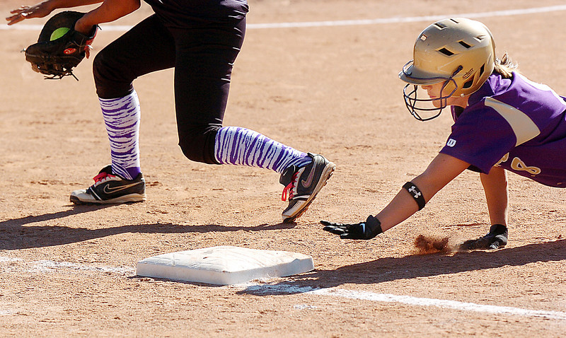 Holy Family's Monique Gonzales reaches out for first base before Middle Park's first baseman during state regional play at the Broomfield Industrial Park on Saturday.<br /> <br /> October 16, 2010<br /> staff photo/David R. Jennings