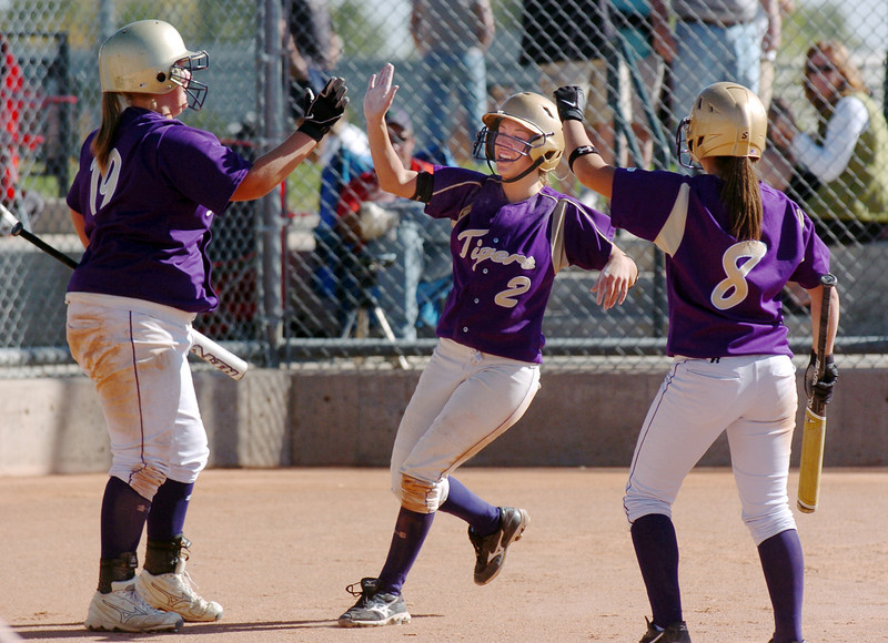 Holy Family's Beth Peterson, center, gets a high five from Caitlyn Krenz and Moniquie Gonzales making an in the park home run against Middle Park  during state regional play at the Broomfield Industrial Park on Saturday.<br /> <br /> October 16, 2010<br /> staff photo/David R. Jennings